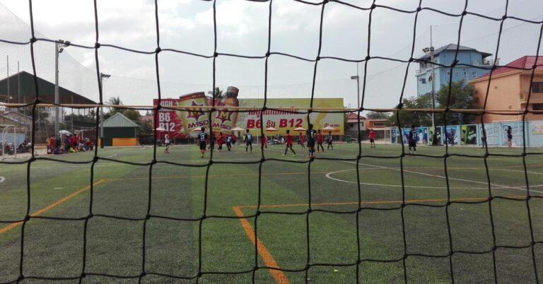 Zwei Schulmannschaften spielen auf einem Kunstrasenplatz Fußball.