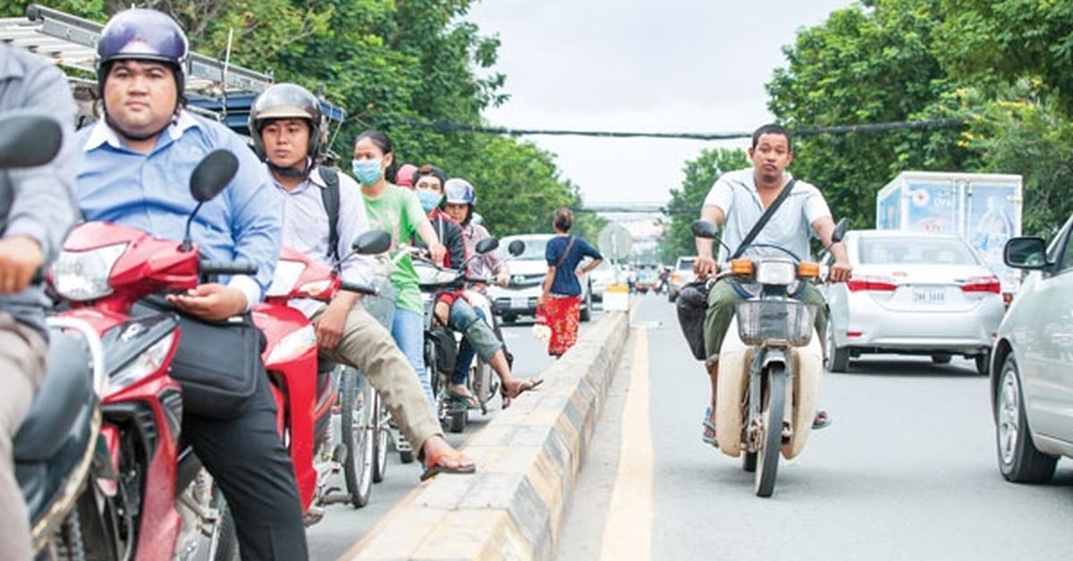 Motorradfahrer warten an einer roten Ampel in Phnom Penh.