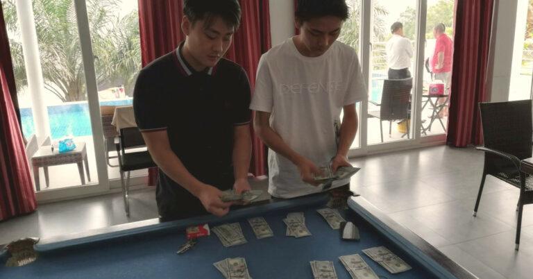Zwei Chinesen zählen Dollarnoten.