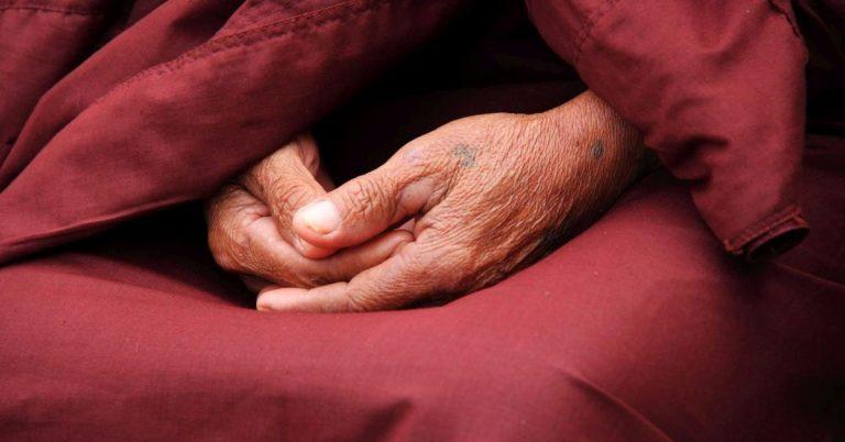 Ein buddhistischer Mönch in dunkelroter Robe.