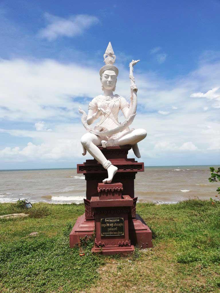 Eine weiße Statue mit dem Meer im Hintergrund.