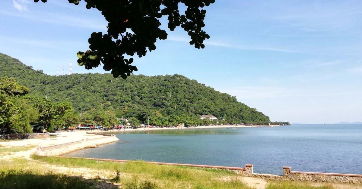 Blick auf Bucht mit Strand und bewaldete Hügel.